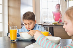 Siblings having breakfast at table with mother preparing food in background Stock Photos