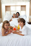 Siblings having breakfast with their parents. Lying on the bed Royalty Free Stock Photo