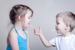 Siblings having fun with lollypops - little royalty free stock images