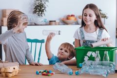 Siblings having fun. While segregating waste at home royalty free stock image