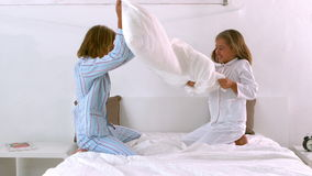 Siblings having a pillow fight on the bed Royalty Free Stock Photo