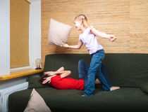 Siblings having pillow fight on a couch Stock Photos