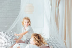 Siblings having pillow fight. Cute siblings having pillow fight, playing on bed royalty free stock photo