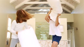 Siblings having pillow fight together. On bed stock video footage