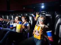 Siblings Having Snacks In 3D Movie Theater. Siblings having snacks while watching 3D movie in cinema theater Stock Photo
