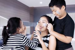 Siblings having time doing face painting to mother Stock Photo
