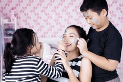 Siblings having time doing face painting to mother Royalty Free Stock Images