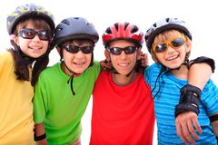 Siblings with helmets. Portrait of four siblings wearing helmets and protective eye wear, isolated on a white background Stock Image