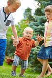 Siblings helping baby to learn first steps. Two proud siblings helping baby to learn first steps in a garden Royalty Free Stock Photos
