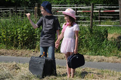 Siblings hitchhiking. For a ride into the summer holiday Royalty Free Stock Image
