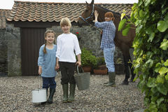 Siblings Holding Buckets With Mother And Horse By Stable Stock Images