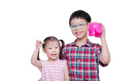 Siblings holding coin and piggybank over white Stock Photos
