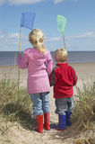 Siblings Holding Fishing Nets On Beach Stock Images