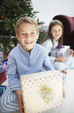 Siblings Holding Gifts By Christmas Tree Stock Image