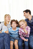 Siblings holding thumbs up between parents Stock Images