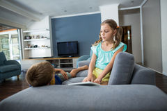 Siblings interacting with each other in living room Royalty Free Stock Photography