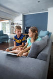 Siblings interacting with each other in living room Royalty Free Stock Image