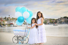 Siblings by lake. Two sisters standing by a baby carriage with dozen of white and blue balloons Royalty Free Stock Images