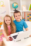 Siblings with laptop computer in their room. Little boy and girl with laptop computer in their room smiling to the camera Stock Photography