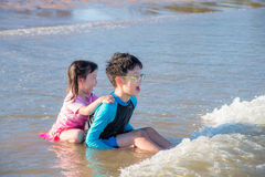 Siblings laughing happily after being hit by the sea Royalty Free Stock Photos