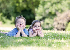 Siblings laying on the grass Stock Image