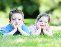 Siblings laying in the grass Stock Images