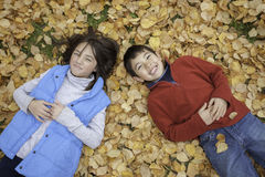 Siblings laying on ground. Stock Images
