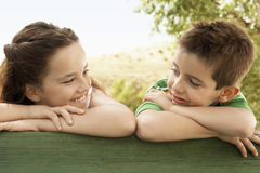 Siblings Leaning Against Wooden Railing Stock Photography