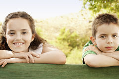 Siblings Leaning Against Wooden Railing Stock Photo