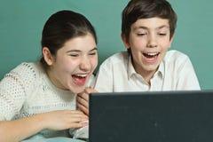 Siblings letten komedie op lengte op laptop royalty-vrije stock fotografie