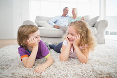 Siblings looking at each other while parents sitting on sofa Royalty Free Stock Images