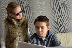 Siblings looking a newspaper Stock Photography