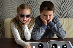 Siblings looking a newspaper. Siblings looking together a newspaper Stock Images