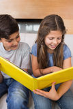 Siblings looking at photo album on sofa in living room Royalty Free Stock Photo