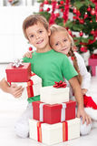 Siblings with lots of presents at christmas time Royalty Free Stock Photo