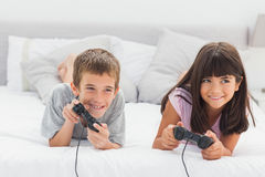 Siblings lying on bed playing video games Royalty Free Stock Photography