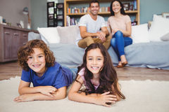 Siblings lying on carpet against parents siting on sofa. Portrait of happy siblings lying on carpet against parents siting on sofa Royalty Free Stock Photography