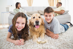 Siblings lying with dog while parents relaxing on sofa Royalty Free Stock Photo