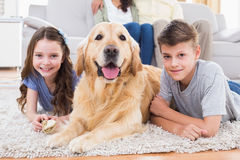 Siblings lying with dog while parents relaxing on sofa Royalty Free Stock Images