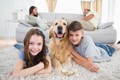 Siblings lying with dog while parents resting  on sofa Royalty Free Stock Image