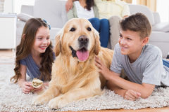 Siblings lying with dog while parents sitting on sofa Stock Image