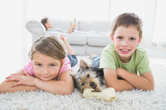 Siblings lying on rug with yorkshire terrier smiling at camera Stock Photos
