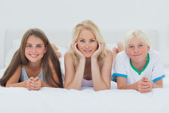 Siblings and mother lying on bed Royalty Free Stock Photography