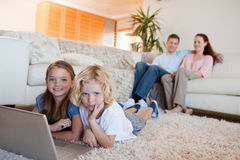 Siblings with notebook on the floor Stock Photo
