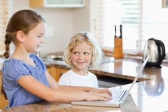 Siblings on the notebook in the kitchen Stock Photos