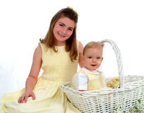 Siblings - One in Basket. Close view of smiling school aged girl and baby brother sitting in basket, looking at camera Stock Photos