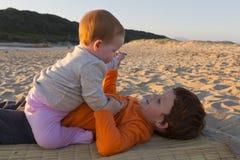 Siblings op het strand Stock Foto's
