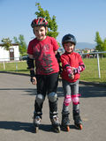 Siblings op rollerskates Stock Foto