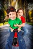 Siblings op stuk speelgoed raceauto Stock Fotografie