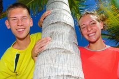 Siblings by palm tree Royalty Free Stock Photo